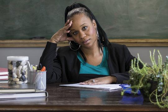 Overwhelmed black female teacher sitting at her desk