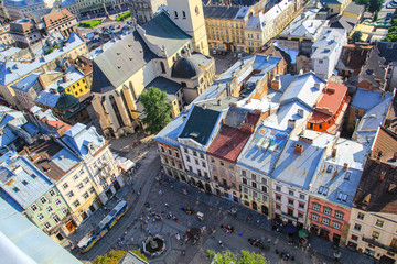 Panoramic view on the old beautiful european city. Medieval architecture with churches, houses, cathedrals and roofs. Summer green photos of ancient Lviv. Amazing town scenery in evening sunset lights
