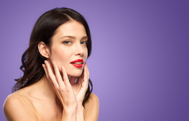 beauty, make up and people concept - beautiful young woman with red lipstick over ultra violet background touching her face