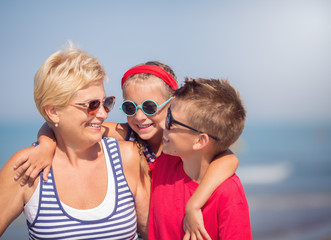Grandmother with grandchildren having fun on the beach