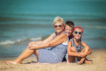 Grandmother with grandchildren having fun on the beach