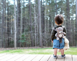 Happy toddler boy playing outside with his teddy bear
