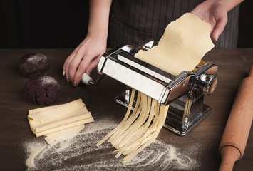 Preparing homemade fettuccine on pasta machine