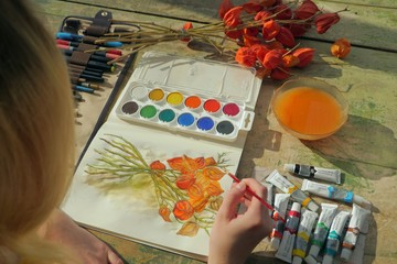 young female artist painting a picture of a red physalis plant in front of her
