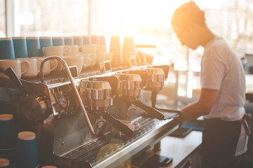A young Barista guy stands behind a coffee machine and prepares fresh espresso, and the window shines a bright sun. Side view with copy space for your text.