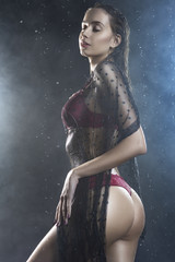 Young wet slim girl wearing a red lingerie and black translucent veil posing sideways in rain water drops in a studio shows her beautiful butt on black in a theatrical smoke
