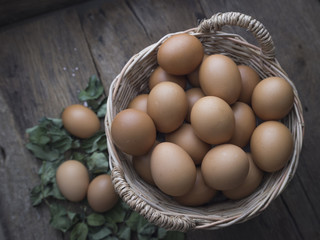 Fresh eggs in basket on old wooden background
