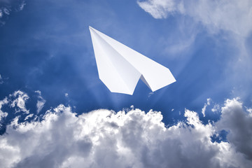 White paper airplane in a blue sky with clouds. The message symbol in the messenger
