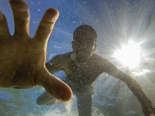 Man diving and grabbing something underwater with his hand Wall mural