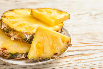 Plate with fresh pineapple slices on wooden background