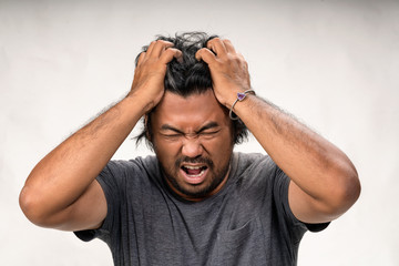 Scream stress closeup portrait of asian upset unhappy angry bearded depressed man yelling wide open mouth squeezing head with hands suffering from headache/tension. Negative emotion face expression.