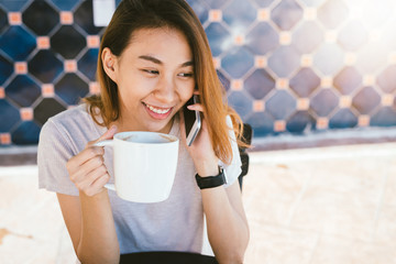 Happy smile asian business women using talking cell phone sitting in cafe and holding a cup of coffee. Beautiful cheerful asian woman at cafe talking on phone and smiling while enjoying coffee.