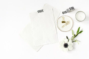 Wedding, birthday desktop mock-up scene. Blank cotton paper greeting cards, washi tape and golden clips. Olive branch and anemone flower.White table background. Flat lay, top view. Feminine stationery