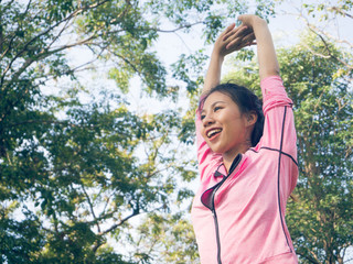 Asian young woman warm up the body stretching before morning exercise and yoga in the park under warm light morning. Healthy young asian woman exercising at park. Woman exercise outdoor concept.