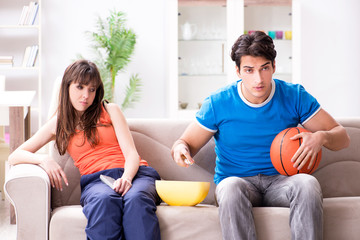 Man watching basketball with his wife