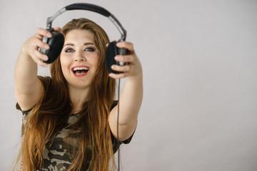 Teen women holding headphones