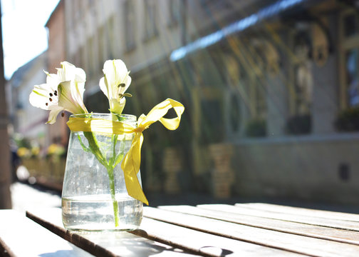 A table with flowers of a street cafe, a soft focus. Free space.