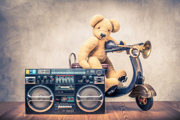 Retro ghetto blaster radio cassette tape recorder and Teddy Bear on old black toy scooter from circa 80s front concrete textured wall background. Listening music concept. Vintage style filtered photo