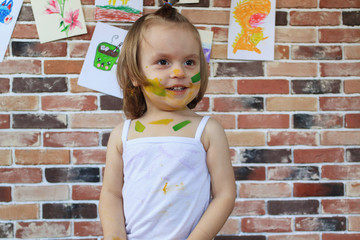 Beautiful little smiling baby girl with face painted in colorful paints