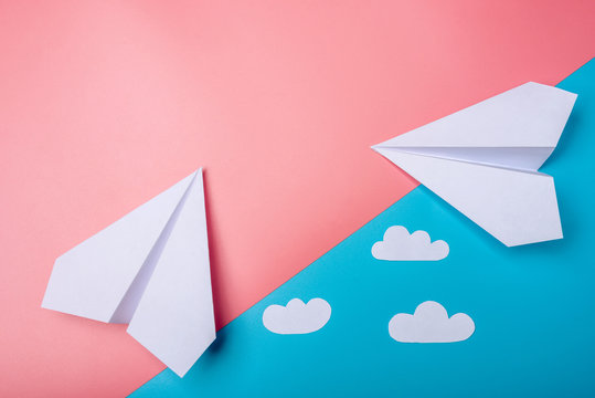 White paper origami airplane with clouds lies on pastel blue background