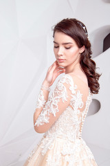 Attractive caucasian woman wearing in luxurious long wedding dress. Concept of wedding hairstyle, makeup and accessories.