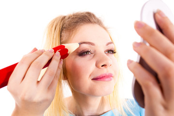 Woman painting eyebrows using regular pencil