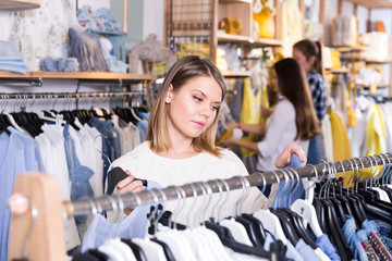 Woman customer looking  blue shirt  in the fashion store