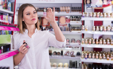 Girl choosing new nail polishes in cosmetics store