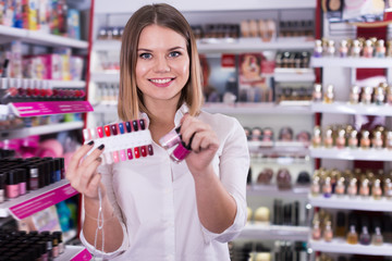 Cheerful seller offering colors of nail varnish