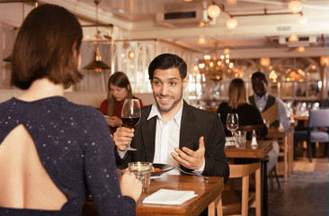 Cheerful man with female in restaurant