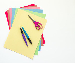 turquoise and purple paint pens and a pair of child's scissors on top of multicolored construction paper sheets isolated on white