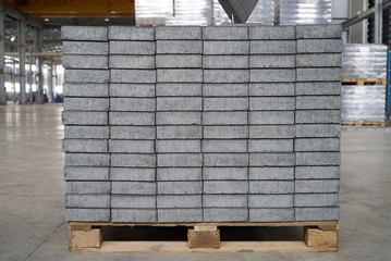 Concrete or cobble gray square pavement slabs or stones for floor, wall or path stacked on wooden pallet in factory warehouse. Industry manufacturing concept