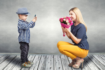 Little boy taking pictures on a mobile phone your mom with a bouquet of roses.Spring, concept of family vacation. Women's day,mother's day.