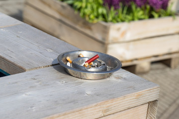 silver ashtray with cigarette butts on a wooden table outside on an sunny summer day