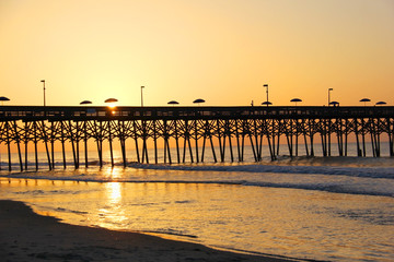 Marine Morning Landscape With Sun Rising Over The Wooden Pier With  Silhouettes Of Fishermen And Umbrellas