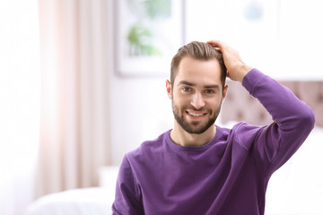 Portrait of young man with beautiful hair indoors