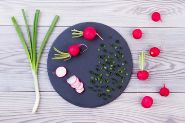 Spring onion and radishes on slate board. Top view on red radishes and green organic onion on wooden background. Food for vegans.