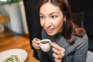 Young eastern woman drinking strong aroma coffee in a cafe