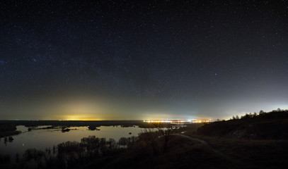 Sky with the stars in the landscape with a pond. Night landscape with a lake.