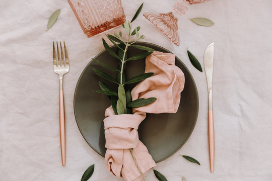 Rustic table setting. Table decorations with linen napkin, olive branch. Top view. Flat lay.  Wedding or holiday concept
