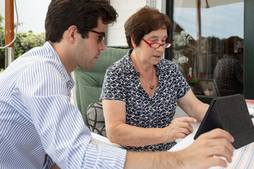 Grandson helping grandma with digital tablet