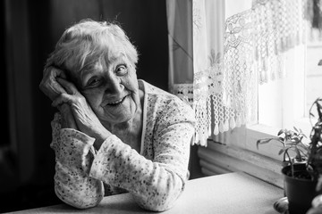 Black and white portrait of an elderly positive woman 75-80 years old.