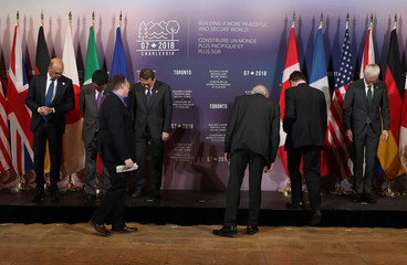 Security ministers and foreign ministers search for their name tags prior to a group photo during meetings for foreign ministers from G7 countries in Toronto