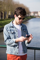 Young man using mobile phone while standing on bridge