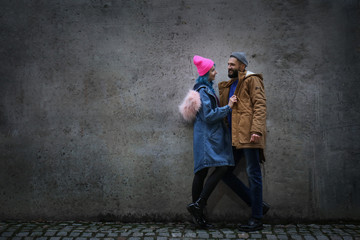 Young hipster couple near grey wall outdoors