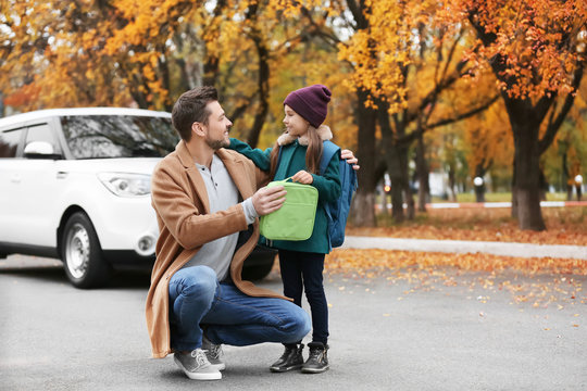 Young man giving lunch bag to his daughter before school