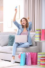 Emotional woman with credit card and laptop at home. Online shopping concept