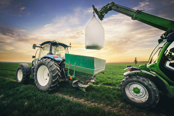 Fototapete - sequence of work of machinery for transporting fertilizers in the field in the spring