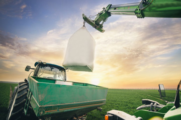 Wall Mural - crane transfers the fertilizer sack to the tractor trailer in the field in the spring
