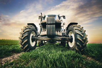 Wall Mural - professional tractor with big tires is moving along the road in the field in the spring